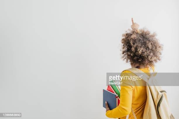visão traseira de uma garota afro-americana bonita segurando livros escolares um apontando em um espaço de cópia - copy space - fotografias e filmes do acervo