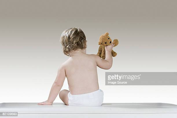 Rear view of a baby girl and a teddy bear