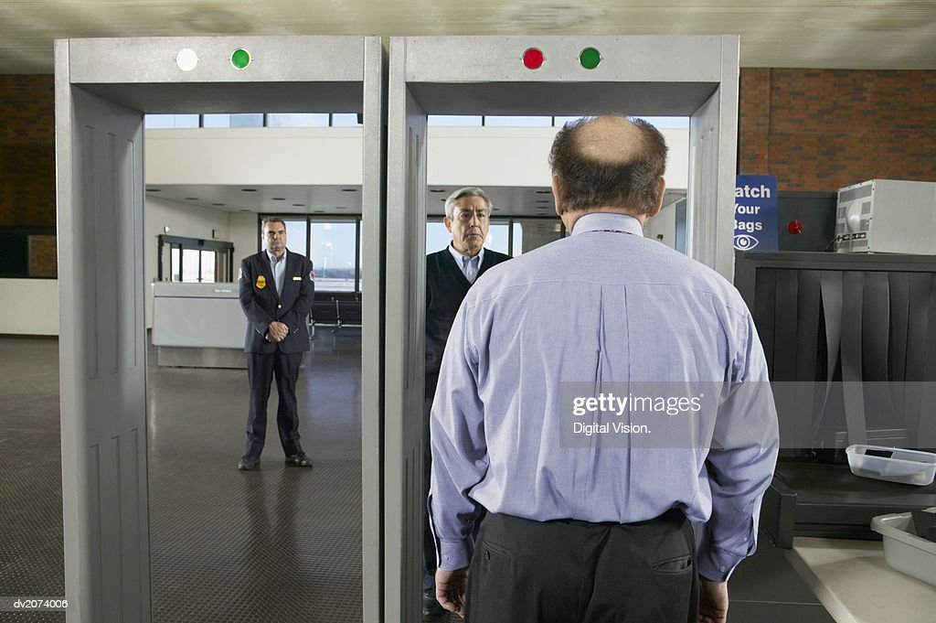 Rear View of a Balding Man Walking Through an Airport Metal Detector : Stock Photo