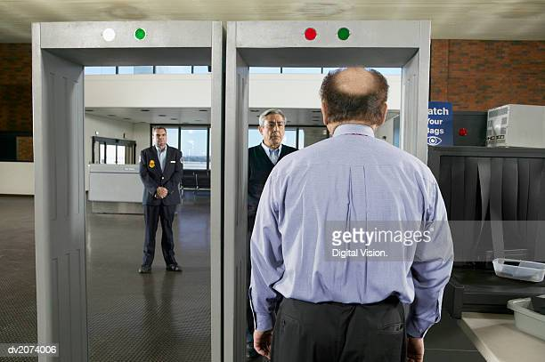 Rear View of a Balding Man Walking Through an Airport Metal Detector
