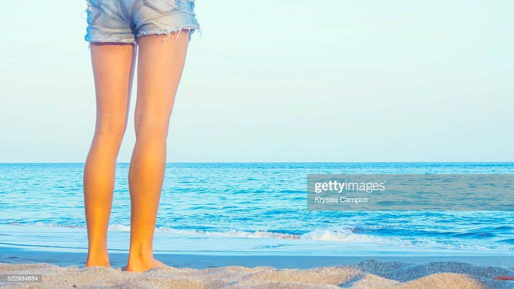 Rear view of a beautiful girl standing in front of a deep blue sea : Stock Photo