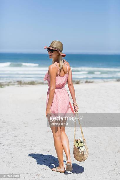 rear view of a beautiful woman walking on the beach - woman carrying tote bag stock photos and pictures