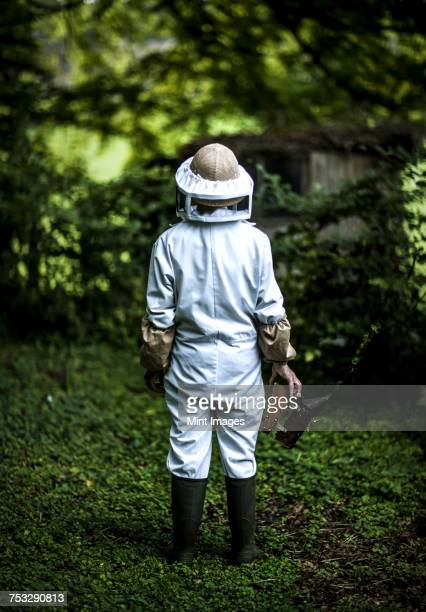 Rear view of a beekeeper in a protective bee keepers suit and head covering and boots carrying a bee smoker.
