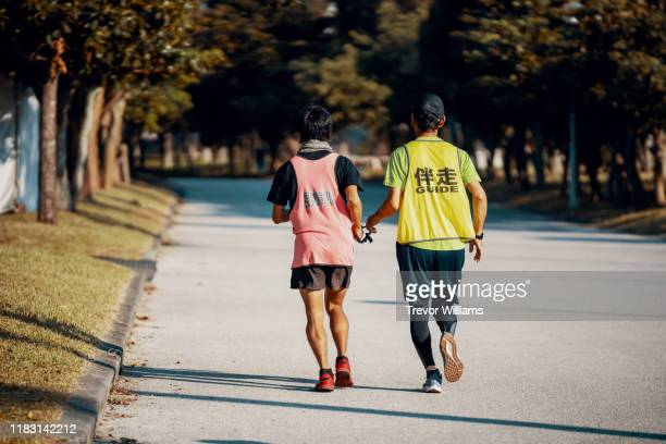 Rear view of a blind marathon athlete running with his guide