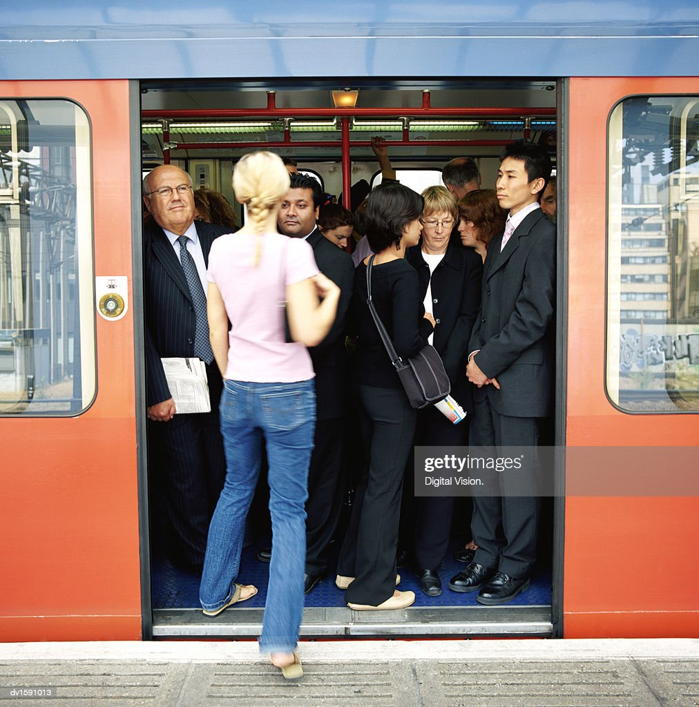 Rear View of a Blonde Woman Stepping Onto a Crowded Commuter Train : Stock-Foto