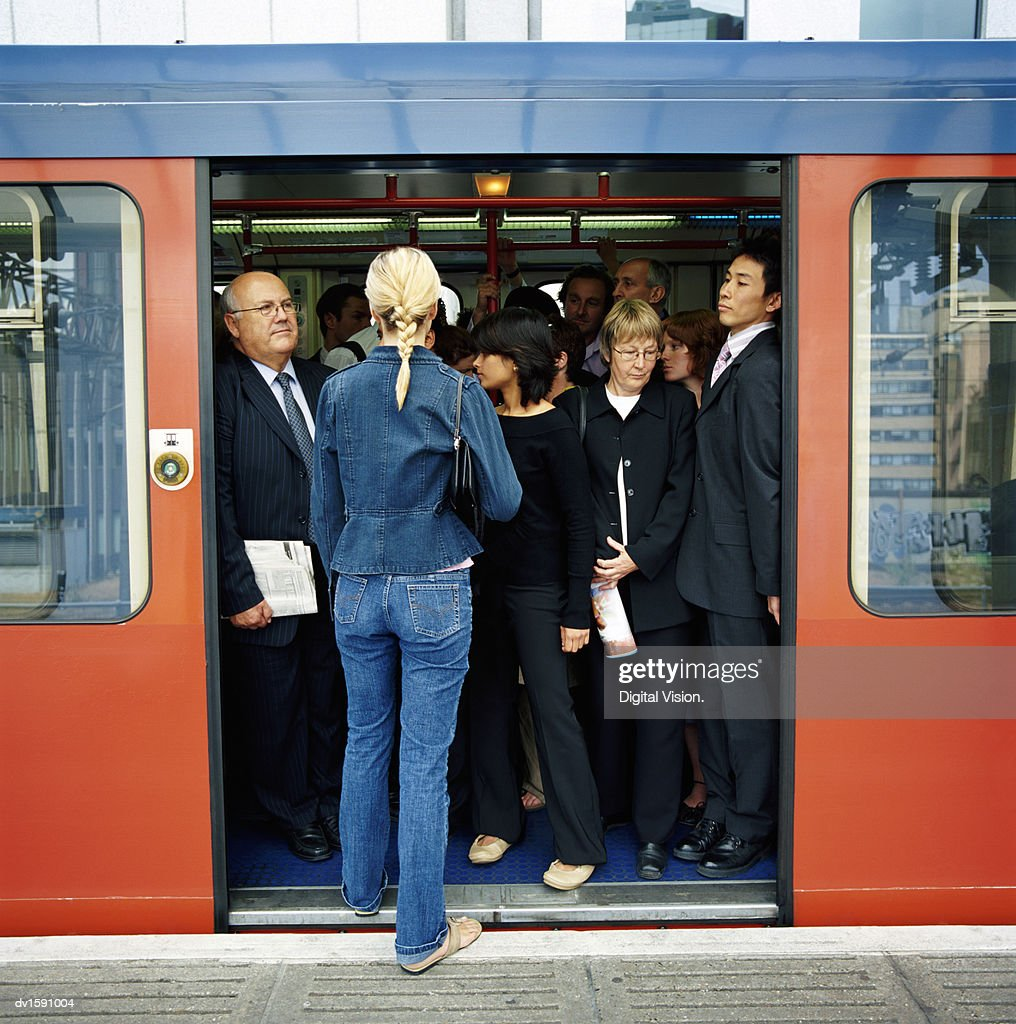 Rear View of a Blonde Woman Trying to Board a Crowded Train : ストックフォト