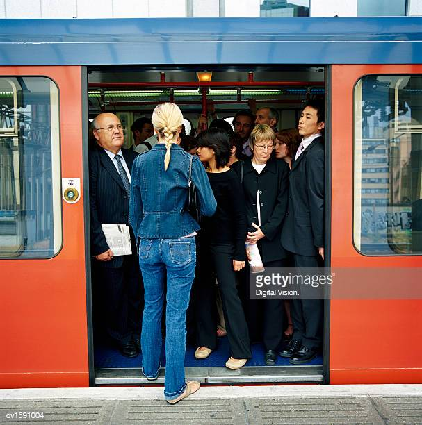 rear view of a blonde woman trying to board a crowded train - beengt stock-fotos und bilder