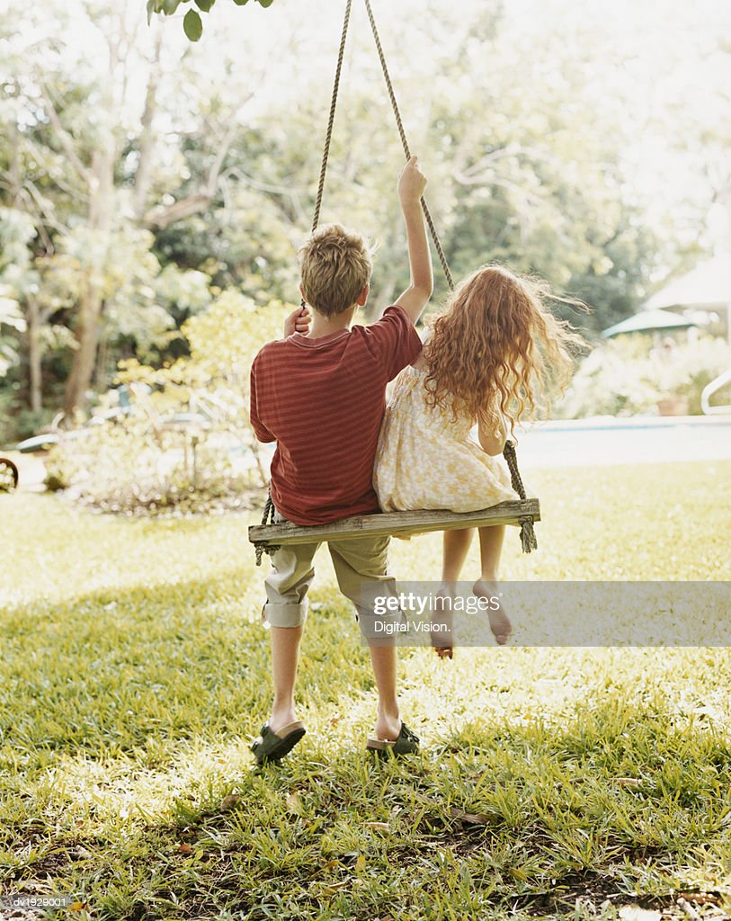 Rear View of a Boy and a Girl Sitting Side by Side on a Swing : Stock Photo