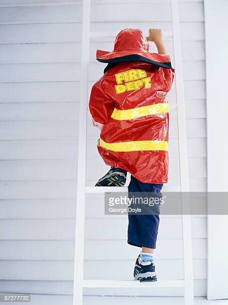 Rear view of a boy climbing up a step ladder, pretending to be a fireman