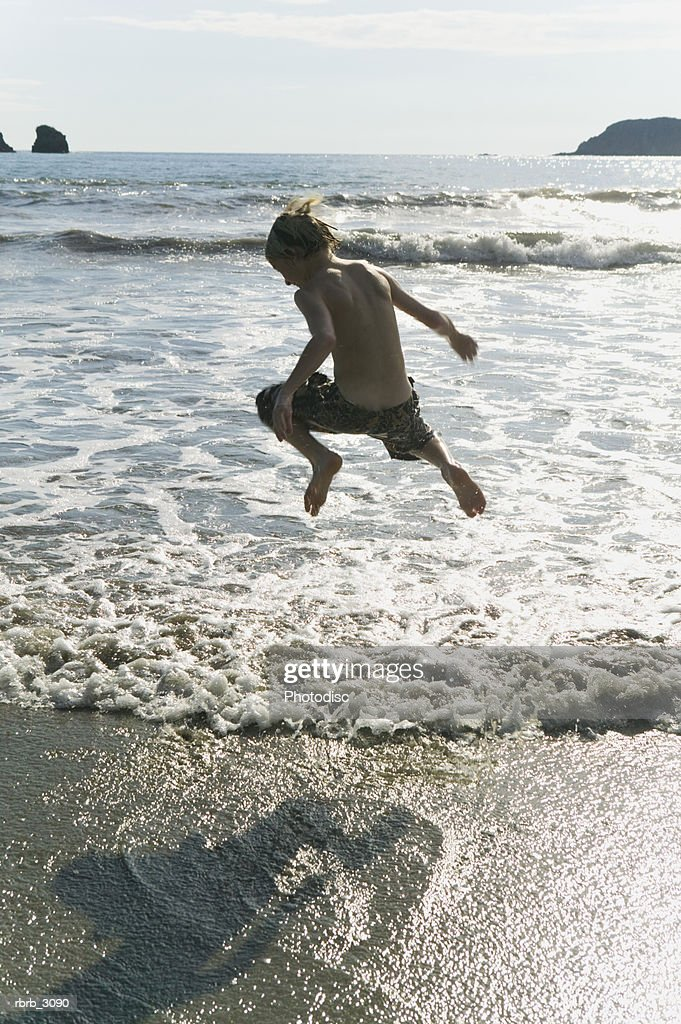 Rear view of a boy jumping in the sea : Foto de stock