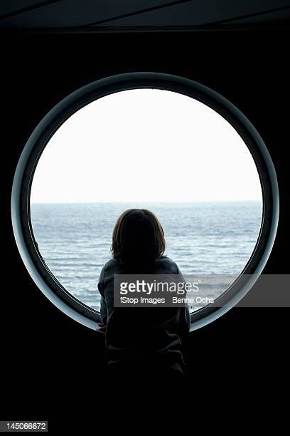 Rear view of a boy looking through a porthole