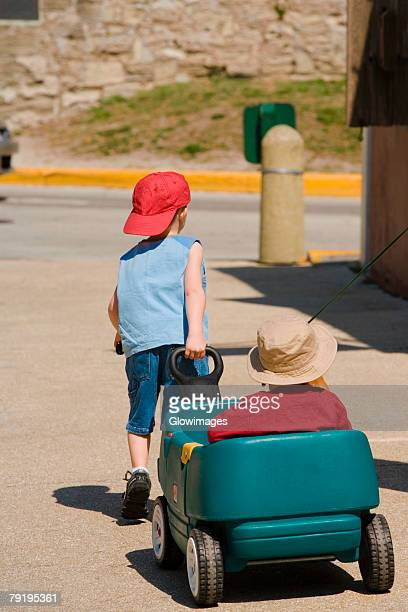 Rear view of a boy pulling a toy car with a baby on it, St. Augustine, Florida, USA