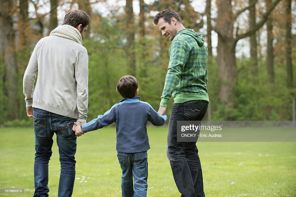 Rear view of a boy walking with two men in a park : Stock Photo