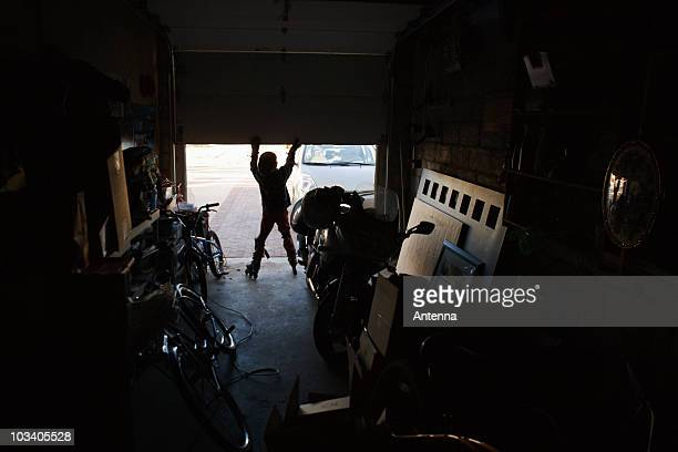 Rear view of a boy wearing rollerblades and opening a garage door