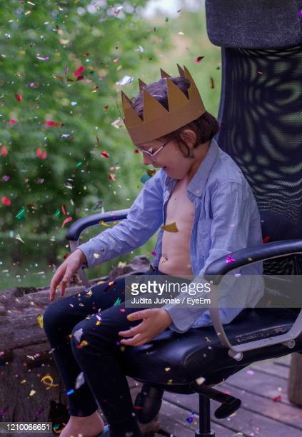 rear view of a boy with crown sitting outdoors - reality kings stock pictures, royalty-free photos & images