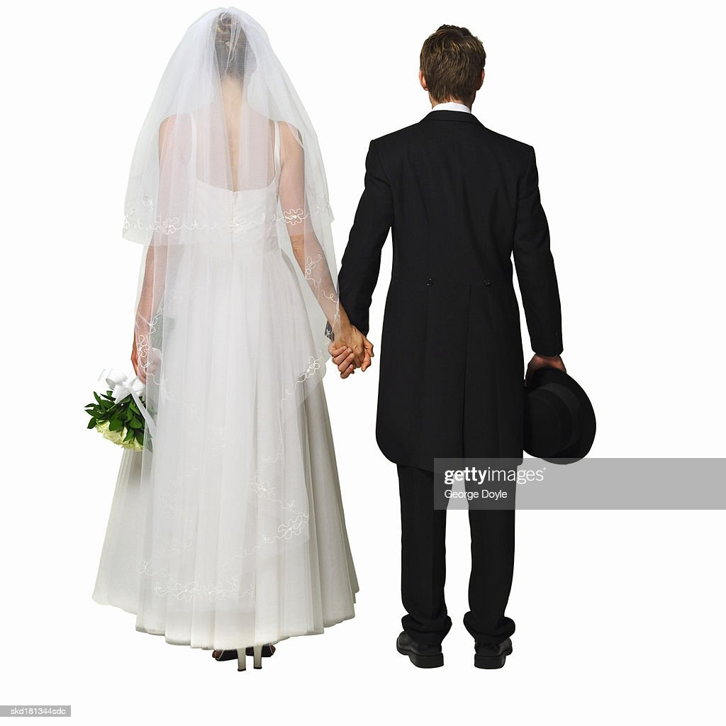 Rear view of a bride holding bouquet and groom holding his hat : Stock Photo