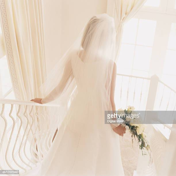 Rear View of a Bride in a Wedding Dress Descending a White Stairway