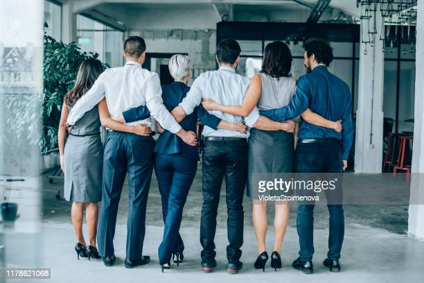 rear view of a business team standing together - arm around stock pictures, royalty-free photos & images