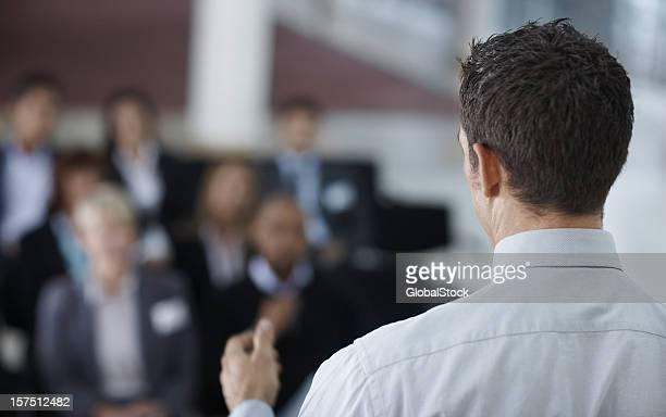 Vue arrière d'un homme d'affaires donnant un discours