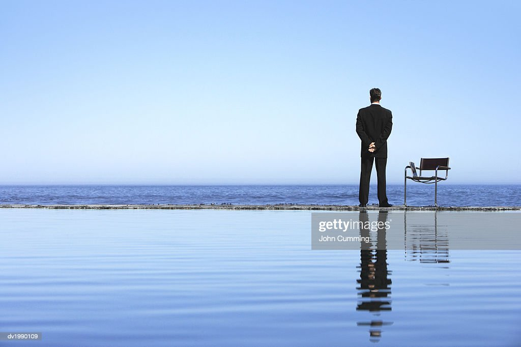 Rear View of a Businessman Looking Out to Sea : Stock Photo