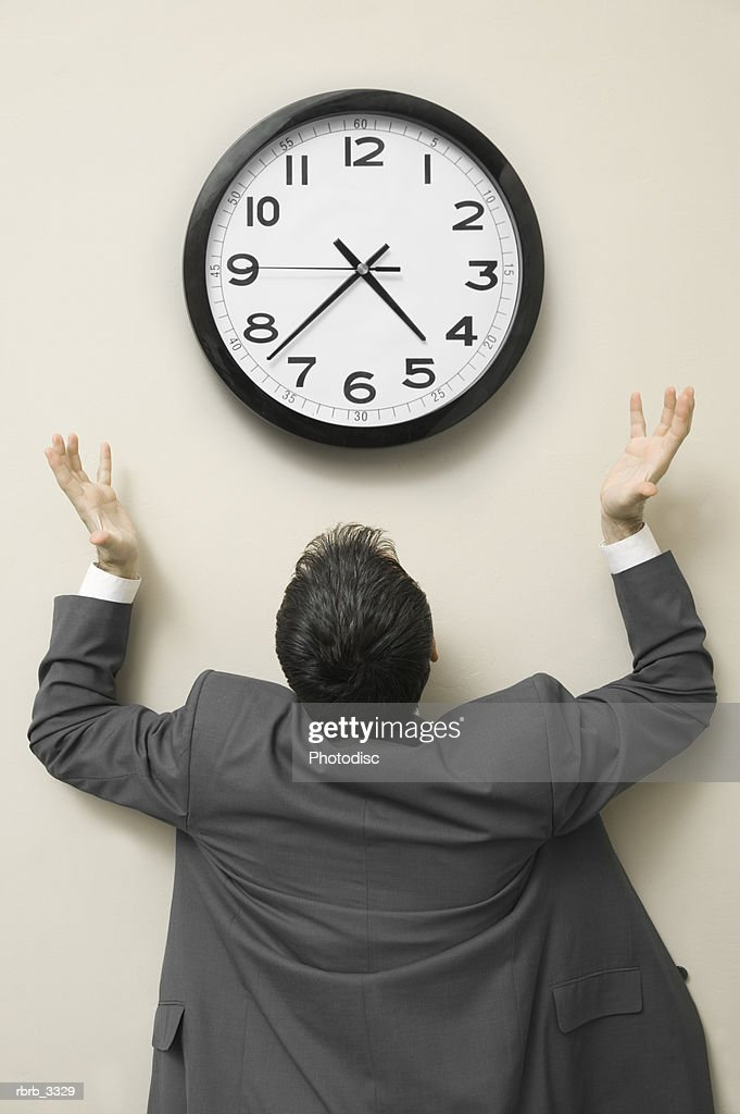 Rear view of a businessman looking up at a wall clock : Foto de stock