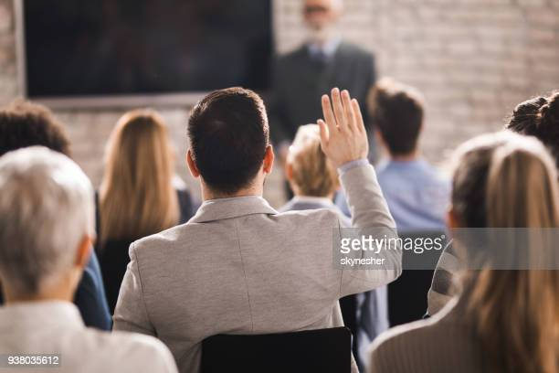 rear view of a businessman raising his hand on a seminar in a board room. - attending stock pictures, royalty-free photos & images