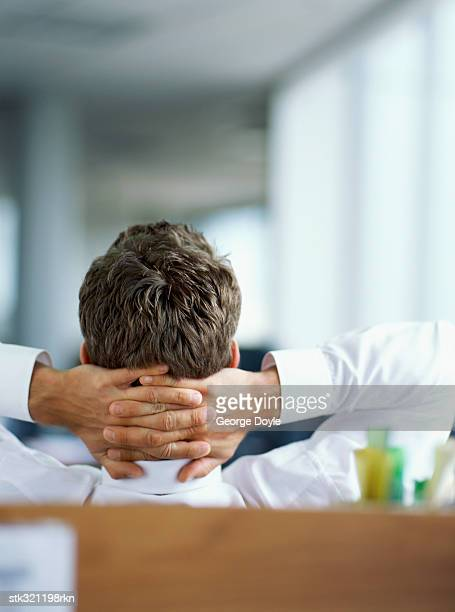 rear view of a businessman relaxing with his hands behind his head in an office