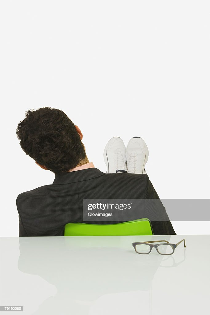 Rear view of a businessman sitting with his feet up in an office : Foto de stock