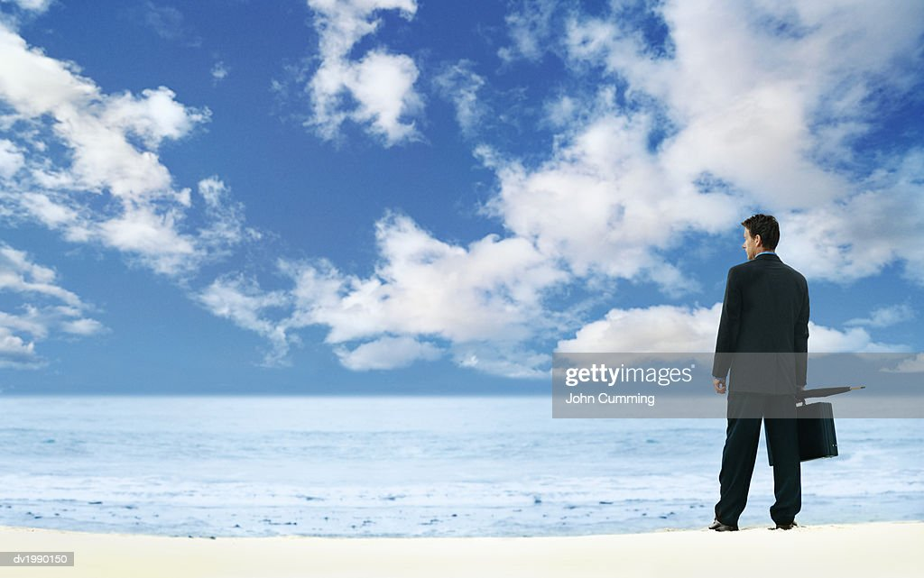 Rear View of a Businessman Standing by the Sea, Looking at the View : Stock Photo