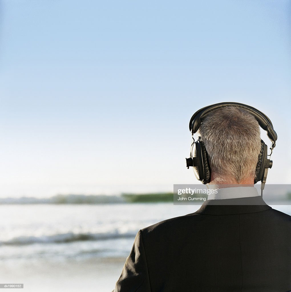 Rear View of a Businessman Standing by the Sea Wearing Headphones : Stock Photo