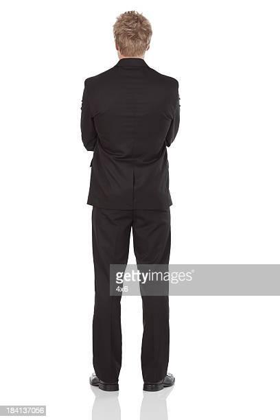 背面ビュー、独立したビジネスマンに腕を組む