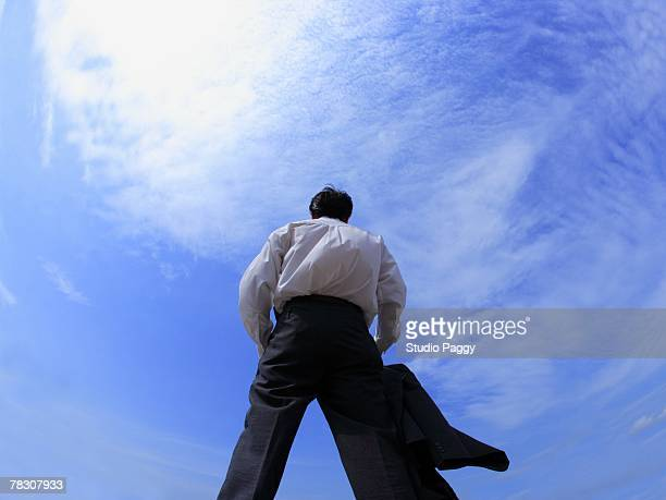 rear view of a businessman standing with his legs apart - benen gespreid stockfoto's en -beelden