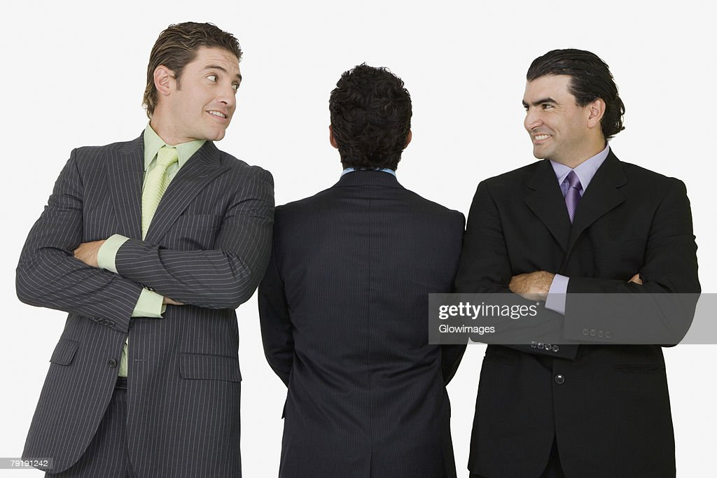 Rear view of a businessman standing with two businessmen with their arms crossed : Stock Photo