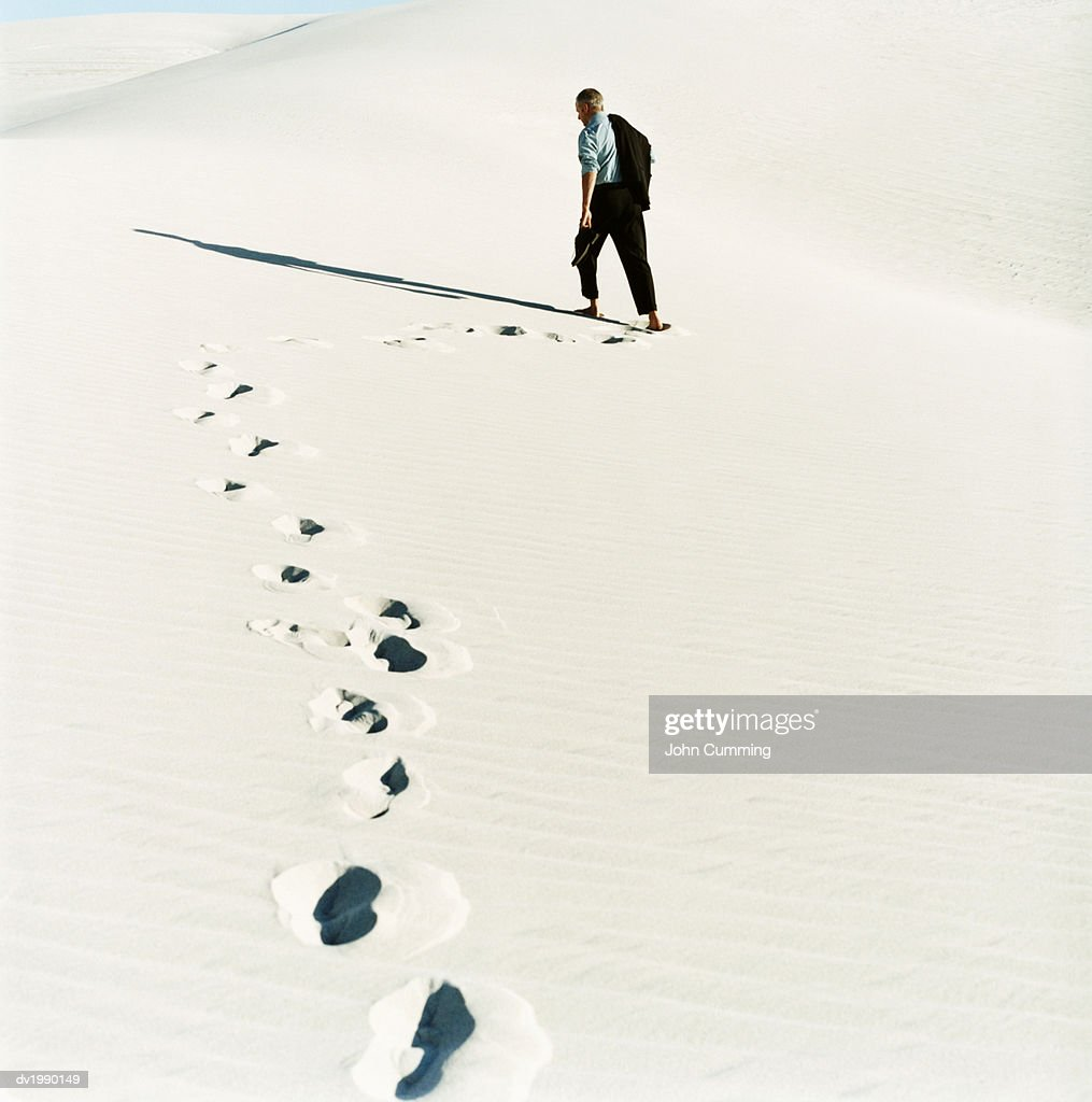 Rear View of a Businessman Walking in the Desert, His Footprints in the Sand : Stock Photo