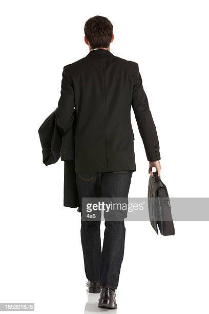 rear view of a businessman walking - coat stock pictures, royalty-free photos & images