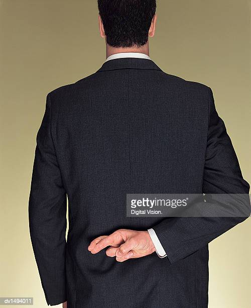 rear view of a businessman with his hand behind his back and his fingers crossed - hands behind back stock pictures, royalty-free photos & images
