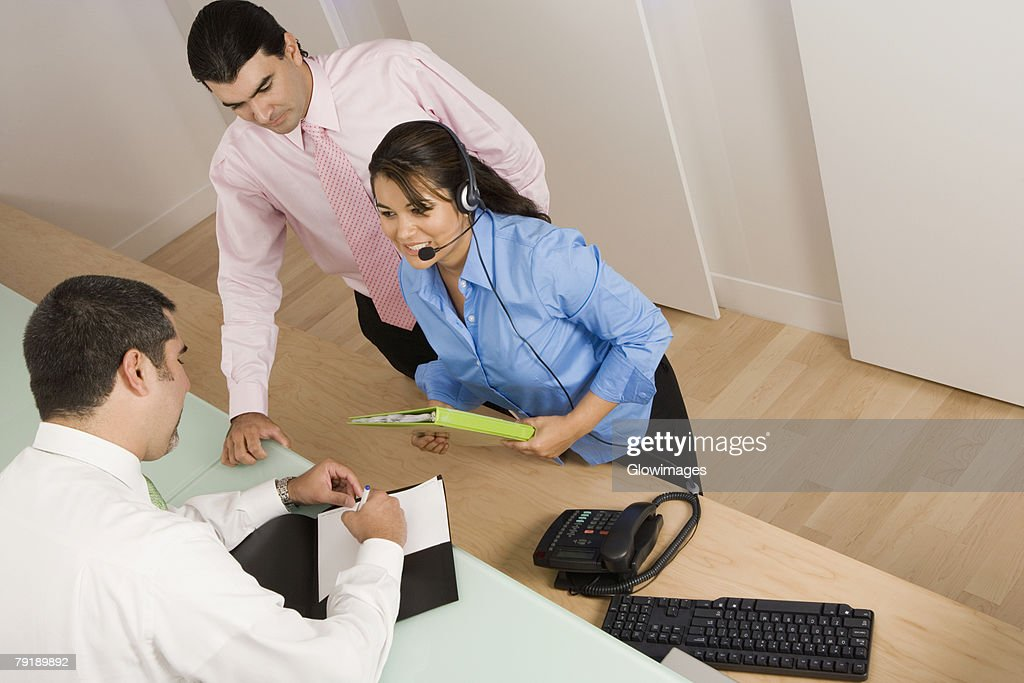 Rear view of a businessman writing with a businesswoman and a businessman looking at him : Stock Photo