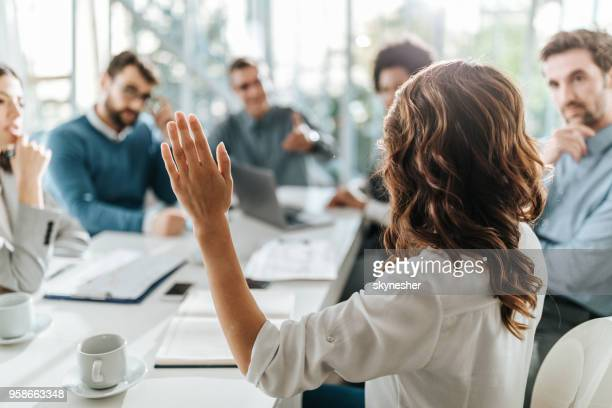 rear view of a businesswoman asking a question on a meeting with her colleagues in the office. - q&a stock pictures, royalty-free photos & images