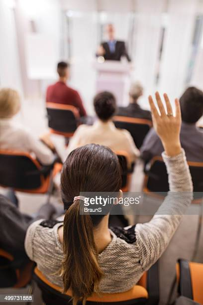Rear view of a businesswoman raising her hand on seminar.