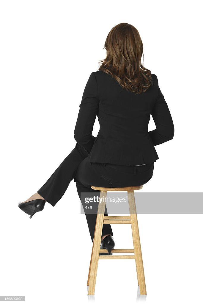 Rear view of a businesswoman sitting on stool : Stock Photo