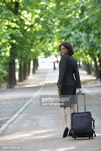 Rear view of a businesswoman walking with a trolley