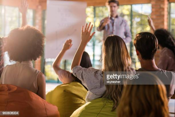 rear view of a businesswoman wants to ask something on presentation at casual office. - q&a stock pictures, royalty-free photos & images