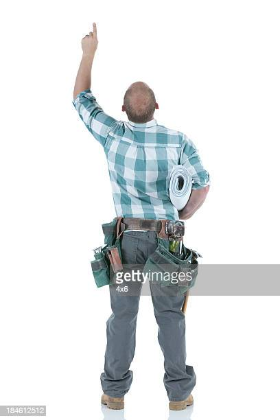 Rear view of a carpenter pointing up