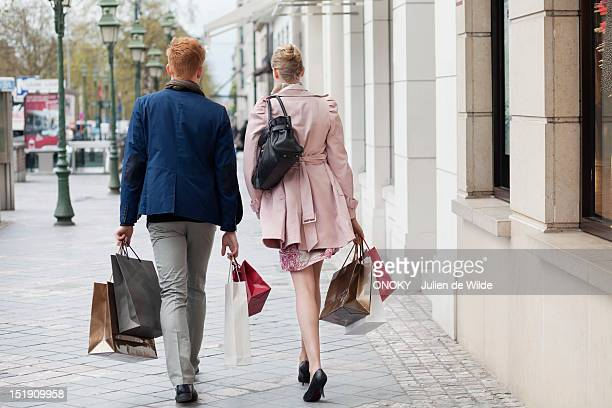Rear view of a couple carrying shopping bags