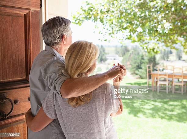 背面ビューのカップルは、手を背に立つ
