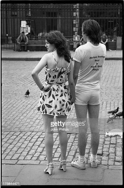 CONTENT] Rear view of a couple holding hands at Covent Garden Piazza London dressed in summer clothes The girl's face is seen in profile Neither have...