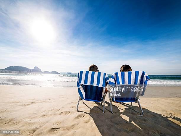 Vista traseira de um casal em cadeiras de lugar na praia.