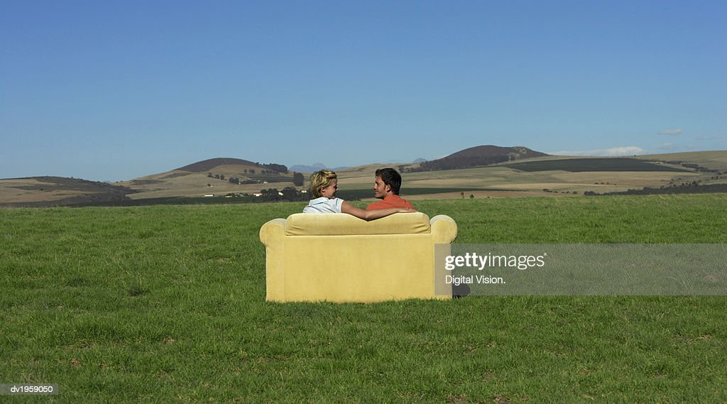 Rear View of a Couple Sitting on a Sofa and Looking at Each Other Face to Face in the Open Countryside : Stock Photo