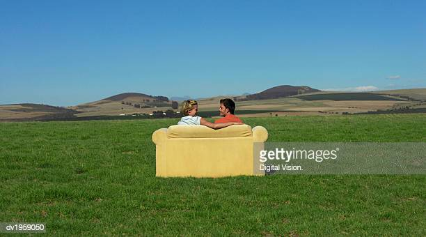 Rear View of a Couple Sitting on a Sofa and Looking at Each Other Face to Face in the Open Countryside