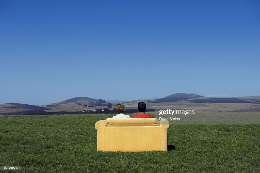 Rear View of a Couple Sitting on a Sofa and Looking at the View of Open Countryside : Stock Photo